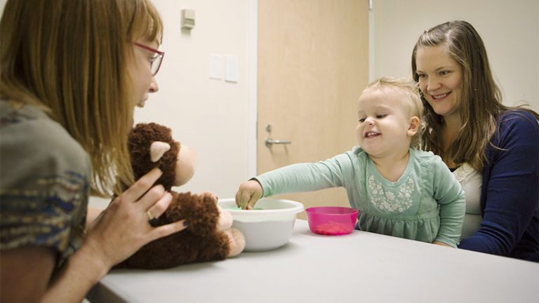 Toddler Gloria Slevinsky sits on her mother Janine Slevinsky's lap across from Kiley Hamlin (left), Canada Research Chair of Developmental Psychology, at UBC in Vancouver. Hamlin's research studies babies and toddlers and sharing. In this experiment Slevinsky was provided with treats that she ccould choose to share with a stuffed toy. (Photograph by Della Rollins)
